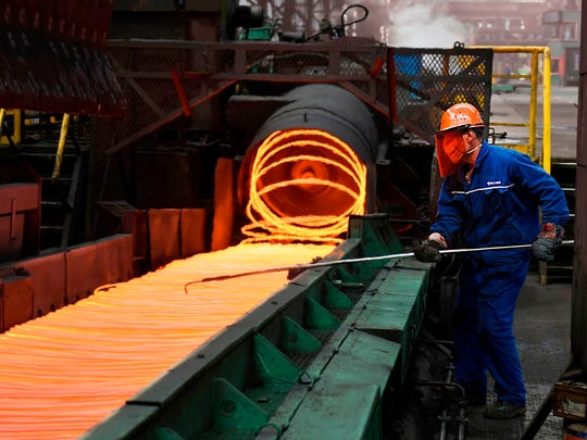 A Chinese employee sorts hot red steel at a steel plant in Zouping in China's eastern Shandong province on March 5, 2018.