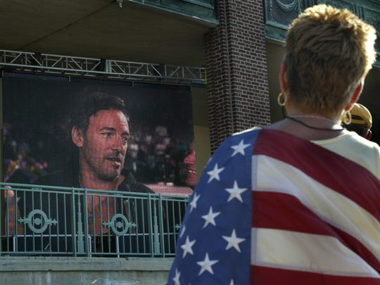 "Margo Pueraro of Bradley Beach is draped in an American Flag as she watches Bruce Springsteen and the E Street Band on the monitors outside Convention Hall during the 2002 broadcast of ""Today"" in which the band performed songs from ""The Rising."""