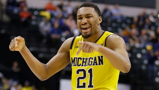 Michigan's Zak Irvin (21) celebrates after scoring a game winning basket during the overtime of an NCAA college basketball game  against Northwestern at the Big Ten Conference tournament, Thursday, March 10, 2016, in Indianapolis. Michigan won 72-70. (AP Photo/Michael Conroy)