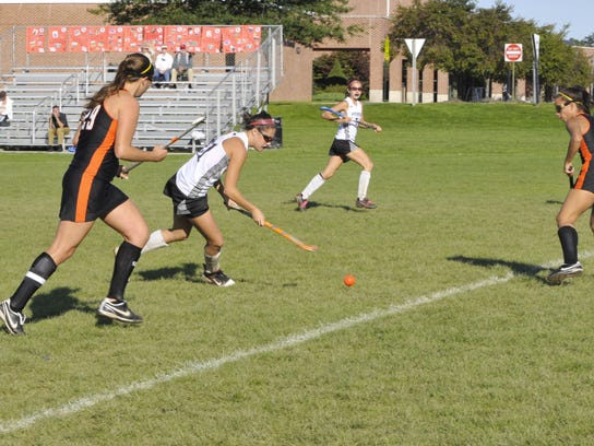 South Western's Katie Wherley dribbles between two Central York defenders.