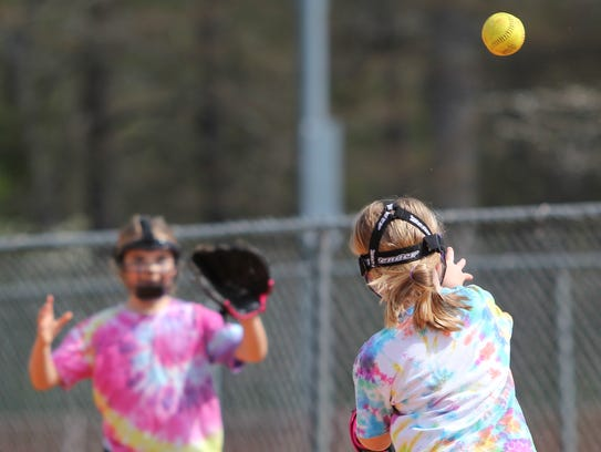 Hannah Hutchins throws to first base after fielding