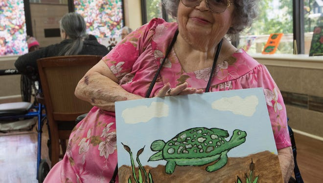 Janice Tolentino shows off some of her art while preparing for an upcoming art show at Arcadia Health and Rehabilitation Center Thursday, May 10, 2018. A variety artworks created by patients at the facility will be on display and up for sale during a fundraiser at the center next week.