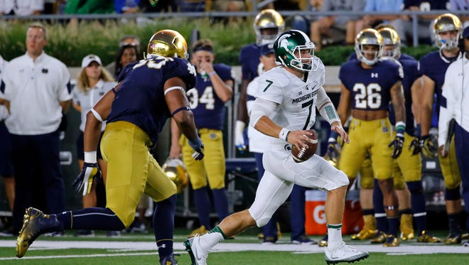Michigan State quarterback Tyler O'Connor scrambles away from Notre Dame defensive lineman Jonathan Bonner during the first half of an NCAA college football game Saturday, Sept. 17, 2016, in South Bend, Ind.
