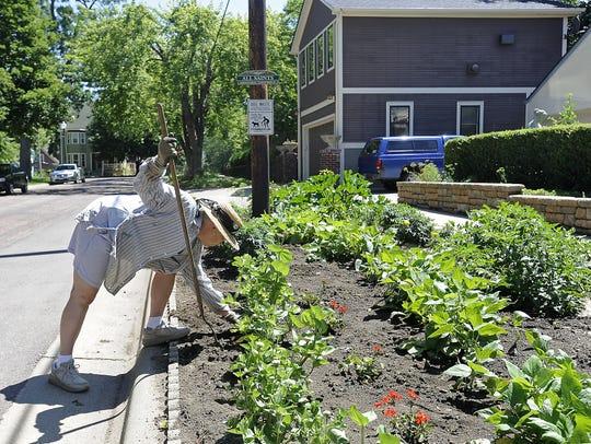 Phyllis Schrag works in her garden on the boulevard