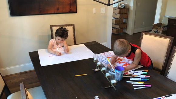 Atlanta mother Shannon Cofrin Gaggero's children, 3 and 6, work on signs for a lemonade stand to support immigrant children separated from their parents at the border.