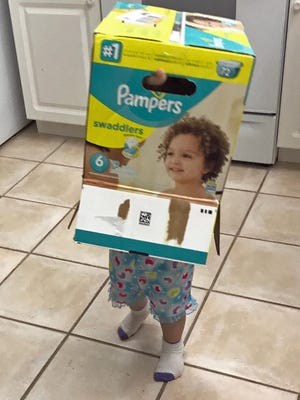 Isabella wanders around the kitchen with a diaper box on her head. She was looking through the box's handle hole to navigate the house.