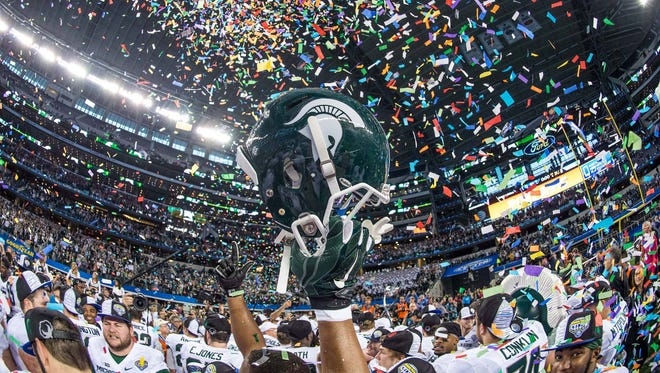 The Michigan State Spartans celebrate the win over the Baylor Bears in the 2015 Cotton Bowl Classic at AT&T Stadium. The Spartans defeated the Bears 42-41.