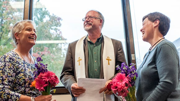 Cathy McGaughey, left, and Diane Ansley are married by Rev. Joe Hoffman, center, during a ceremony at the Buncombe County Register of Deeds office in   October.