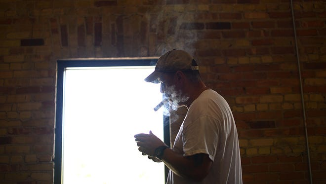 Glen Sherman, co-owner of Prohibition Spirits and Cigar Lounge in downtown Green Bay, lights a cigar.