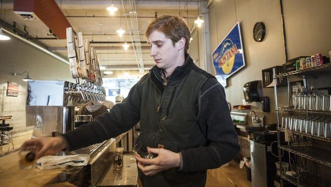 Ethan Kohoutek serves beer at the Ten Mile Creek Brewery in Helena on Wednesday.