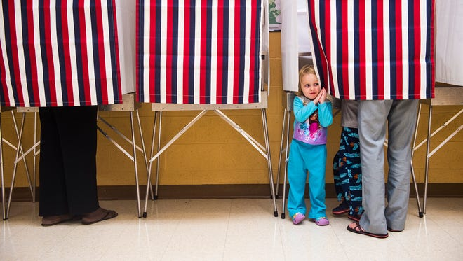 Anna Reid, 3, peeks out of the voting booth as she waits for her mom to finish voting at the Cumberland Township Municipal Building in Gettysburg during the Pennsylvania primaries on April 26, 2016.