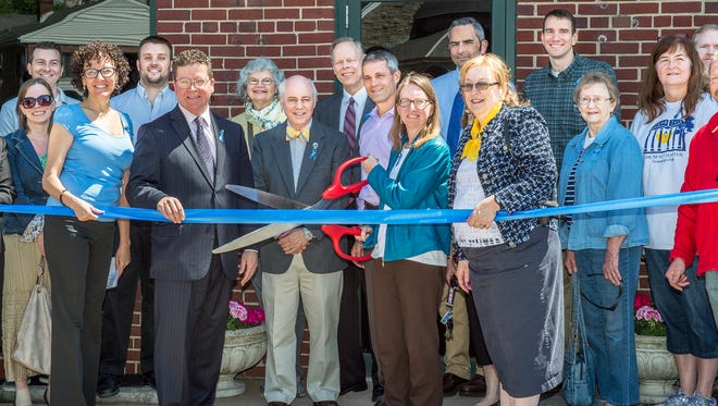 Members of the community come together for the ribbon cutting ceremony for the new temporary location of Coyle Library now located on 340 N. Second Street in Chambersburg, Pa, on Thursday, May 19, 2016. Cole Library is open to the public.