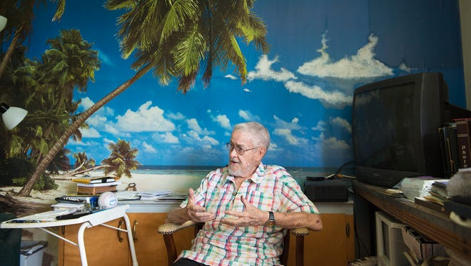 Veteran Chuck Caldwell, 92, sits in front of his beachfront wallpaper in his Gettysburg home, remembering stories from World War II. He enjoys the scenery, as it provides him with a sense of peacefulness - a change from his past at war.