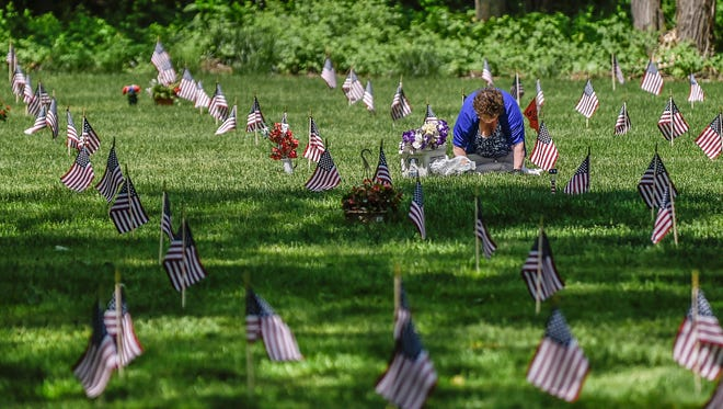 A woman tends to a flag-marked grave at Fort Custer National Cemetery for the Memorial Day observances on Sunday.