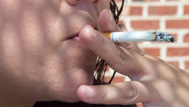 Photo illustration of someone smoking a cigarette smoking.