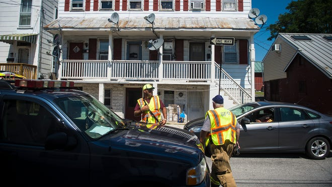 Fire officials and members of the Gettysburg Fire Department work at the scene of a crash caused by a vehicle into a building on Breckenridge Street in Gettysburg on Aug. 28, 2016.