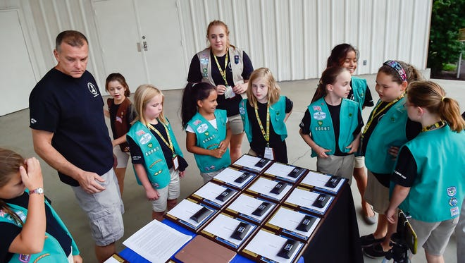 Chambersburg Girl Scout Troop 80067 circle around a table and take a peak at what is on the table before a ceremony honoring them starts on Thursday, Sept. 15, 2016 in Chambersburg, Pa. Troop 80067 sold cookies to raise money for K-9 unit to get bullet proof vests.