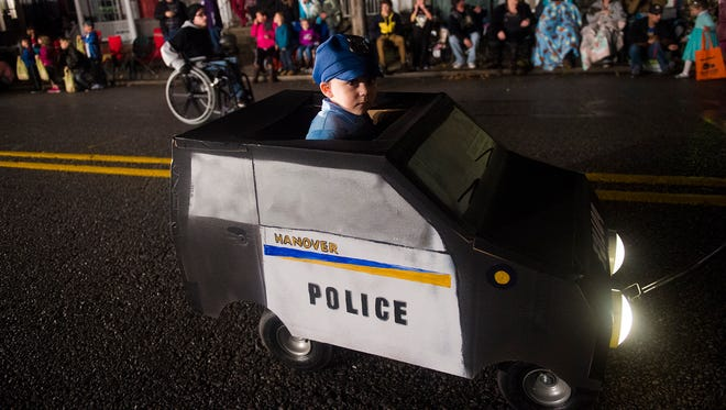 A young Hanover police officer is driven down Baltimore Street during the Hanover Halloween Parade on Oct. 27, 2016.