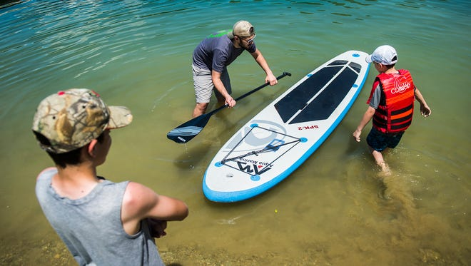 Tannon Hibshman, 12, left, of Hanover, observes as Richard Ellenberger, center, helps Preston Hibshman, 9, learn how to stand-up paddleboard on June 19, 2016 at Codorus State Park.