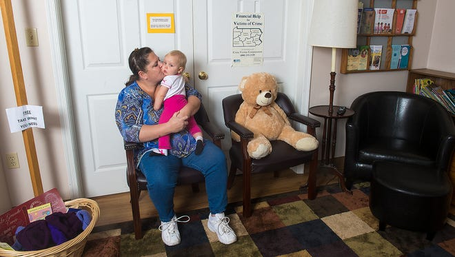 """Hazel Frank, 10 months, gets a kiss from her aunt, Becky Bingel, in the waiting area at Hanover's Safe Home. Bingel has been an emergency hotline volunteer for more than 14 years, working three days a week out of her home, often with Frank at her side. Bingel said her motivation comes in part from remembering what it was like to raise her own son with little money and having to accept housing assistance. She doesn't have much money now, she said, """"but I have time. Instead of just taking, taking, taking, why not give back?"""""""