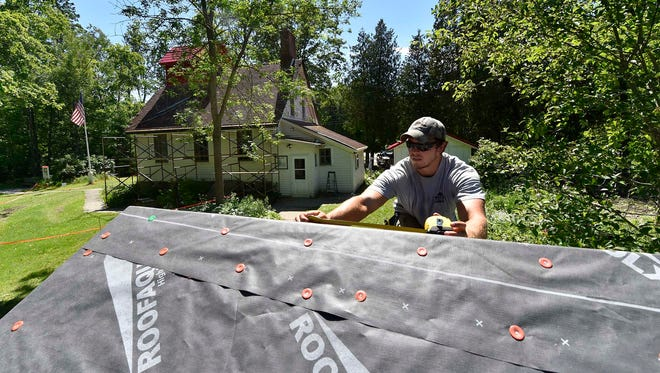 Dustin Veldboom of Peil Construction, Baileys Harbor, works on the under layment of one of four buildings last month comprising the upper and lower range lights at The Ridges Sanctuary, Baileys Harbor. The deteriorating roofs have been replaced with with metal shingles. To see a photo gallery of the renovations, go to: www.doorcountyadvocate.com.