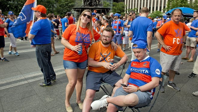 Thousands of FC Cincinnati Soccer fans gathered on Fountain Square on Tuesday, May 29, 2018 to watch a live broadcast from Rhinegeist Brewery announcing that the team was accepted into Major League Soccer. Bri Bacni and Michael Lang of West Chester and Danny Lang of Reading wait for the announcement to begin.