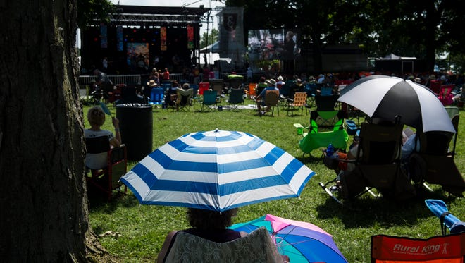 Fans find cover from the sun as Blues 4U band performs during the W.C. Handy Blues and Barbecue Festival at Audubon Mill Park on Friday, June 15, 2018.