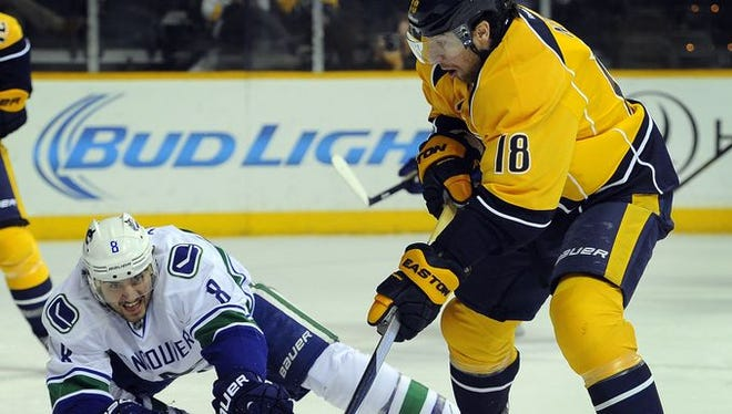 Predators left wing James Neal (18) skates the puck past Canucks defenseman Chris Tanev in the first period Tuesday.