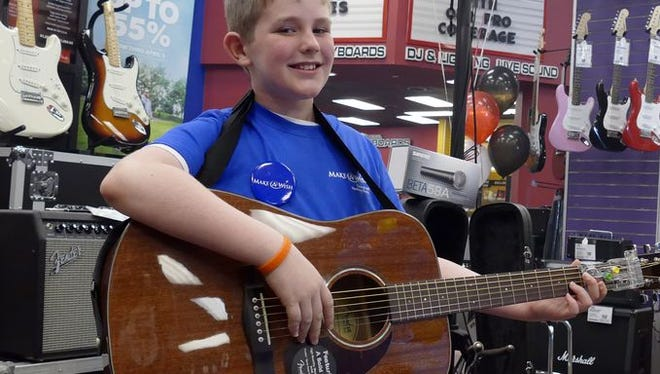Make A Wish recipient, left, Jacob Knott, 10, shows off the guitar he just received from The Guitar Center Saturday afternoon. Jacob has been battling cancer on and off since he was two-years-old.