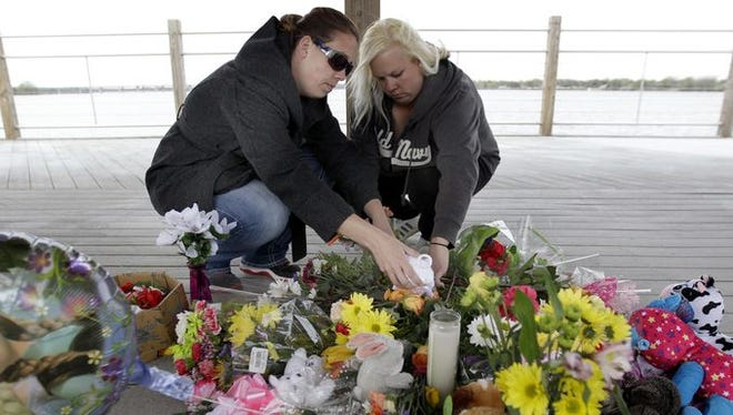 Jodi Meyer, left, and Sonia Meyer place flowers at a memorial in the pavilion on the re-opened Trestle Trail.