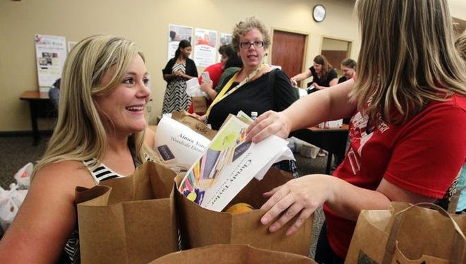 Woodvale Elementary first-grade teacher Aimee Yandle, left, and Woodvale second-grade teacher Christy Taylor pick up school supplies donated by local businesses and individuals as part of The Advertiser's 2014 adopt-a-classroom program.