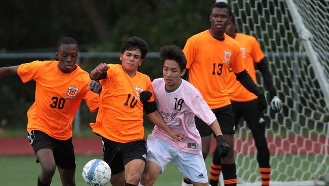 Spring Valley's Shebnaldy Dossous, left, and Jesus Vasquez battle for the ball against Rye's Takizawa Shota in a boys soccer Class A outbracket game in Rye Oct. 23, 2014. Rye won 3-0.