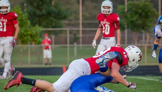 Wisconsin Rapids linebacker Jake Timm, top, tackles an Oshkosh West player during last week's game. Rapids travels to Hortonville Friday.