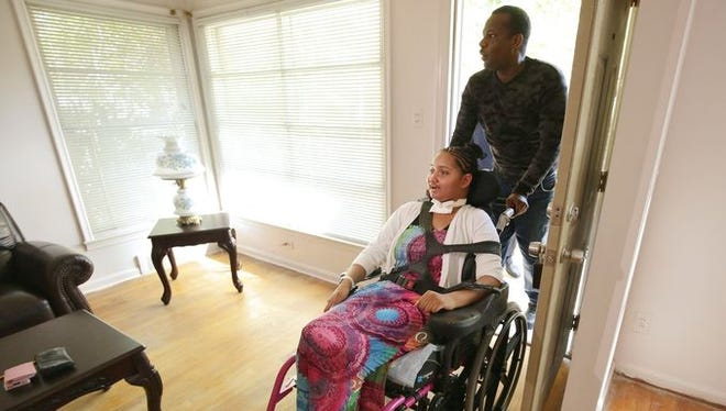 Dreia Davis and her father Curtis White, enter their new home for the first time on Wednesday, September 23, 2015, in Detroit. The handicap-friendly furnished house and a van were donated to the family by Detroit Rescue Mission.