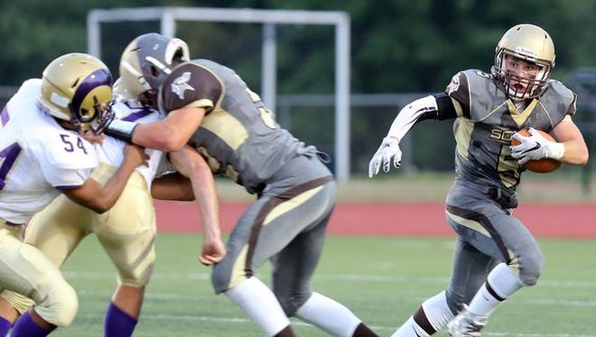 Clarkstown South's Ryan Thomas (5) runs the ball up the field past Clarkstown North's defense during game action at Clarkstown South High School in West Nyack Sept. 4, 2015. Clarkstown North defeated Clarkstown South 26-8.