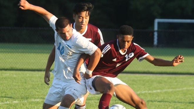 Rye Neck's Luis Galeano, left, tries to get past Valhalla's Jake Son and Ethan Bartlett during their game at Rye Neck Sept. 17, 2015. Valhalla won 2-1.