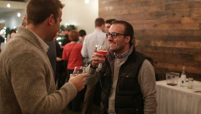 Ryan DeKimpe of Royal Oak, left, and Patrick Sollena of Royal Oak share a toast after getting the Cellarmen's Cranpus mead during the Detroit Free Press Craft Classic beer tasting event on Wednesday Dec. 2, 2015, at the Great Lakes Culinary Center in Southfield. The event featured eight beers and a mead, along with food and trivia.
