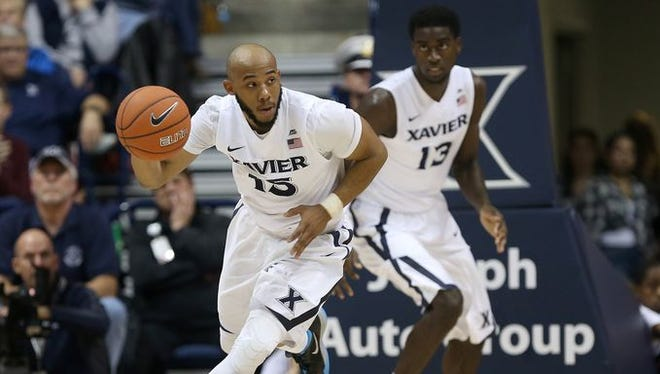 "Myles Davis (left) knew about the Xavier-UC rivalry long before arriving on the Musketeers' campus. Said Davis: ""I compare the Cincinnati-Xavier rivalry to any good rivalry, from North Carolina-Duke to UCLA-Kentucky."""