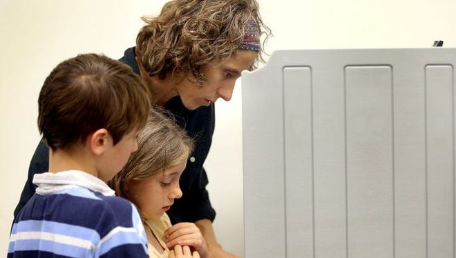 Kelly Parkhurst votes early with two of her children, Keirstan Parkhurst, 9, and Josiah Parkhurst, 11, at the Rutherford County Election Commission office in Murfreesboro on July 18, 2014.