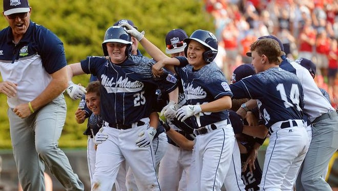 Red Land's Chayton Krauss (25) is surrounded by his teammates after hitting the walk-off run Saturday, Aug. 29, 2015, after the Little League World Series U.S. championship game featuring Red Land Little League of Pennsylvania and Pearland West Little League of Texas, in South Williamsport. Red Land defeated Pearland 3-2 in a walk-off victory to move on to the world championship game against Tokyo Kitasuna of Japan.
