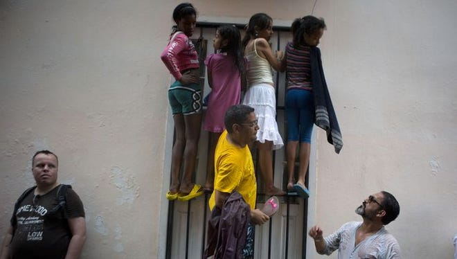 People climb a window grate as they get wet in the rain, in hopes of catching a glimpse of President Obama during his visit to Cathedral Square in Old Havana, Cuba on March 20.