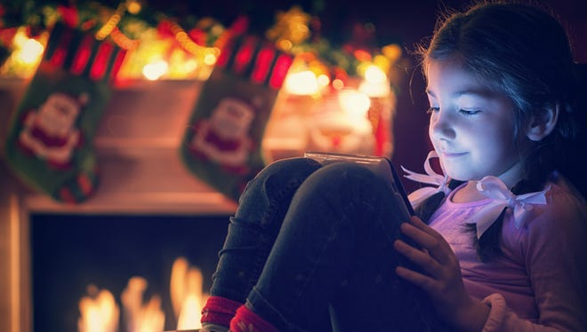 Smiling little girl sitting on the bed at night in front of fireplace at Christmas time. She enjoy while warming,playing and using digital tablet