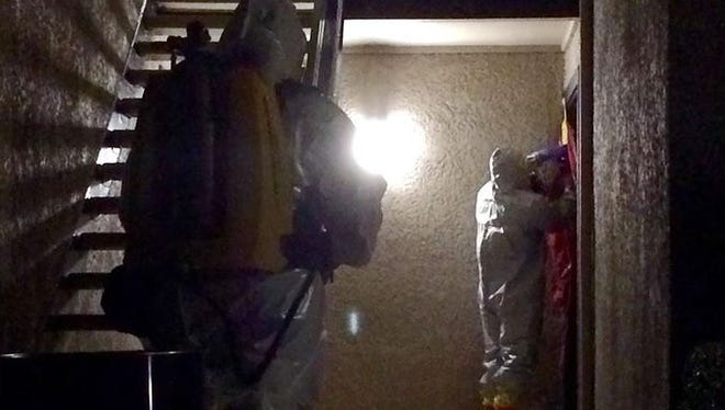 Members of the Dallas Fire-Rescue Haz Mat Unit tapes off the door of a second health-care worker who tested positive for the Ebola virus on Oct. 15 at the The Village Bend East apartments in Dallas. The worker at Texas Health Presbyterian Hospital was monitoring herself for symptoms and reported a fever. She was in isolation within 90 minutes.