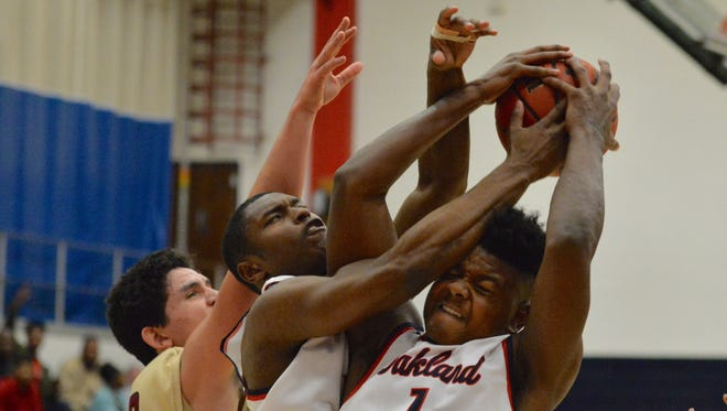 Oakland's Tre Jones (1) battles teammate JaCoby Stevens for a rebound during the Patriots' 52-50 win over Riverdale earlier this season.
