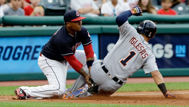Tigers shortstop Jose Iglesias, right, is tagged out at third base by Indians third baseman Jose Ramirez during the third inning Friday in Cleveland.