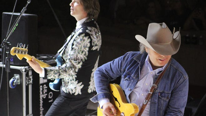 Dwight Yoakam's blue jeans and cowboy hat attire contrasted with his bandmates, who were more flashier during Yoakam's closing set Saturday at the Outlaws & Legends Music Festival.