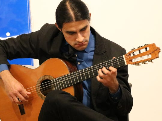 Guitarist Daniel Gaviria performs at the kickoff event Thursday for First Night Burlington. He is part of the Piazzolla Project, which is to perform during the 33rd annual New Year's Eve event from 7-7:40 p.m. at the First Baptist Church.
