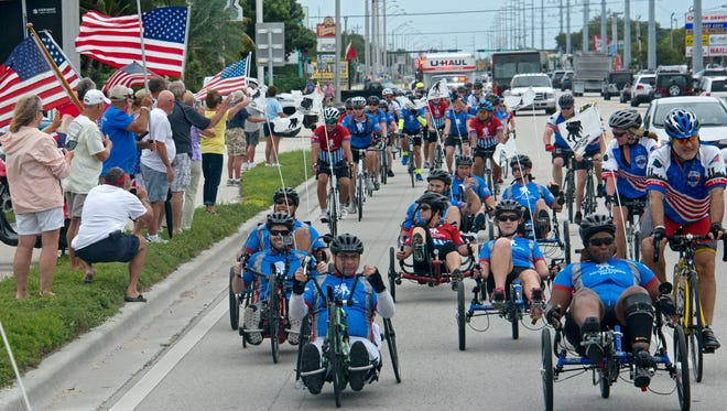 Flag wavers greet wounded soldiers traversing the Florida Keys Overseas Highway in Marathon, Fla., on Jan. 8, 2016 during Soldier Ride, an event staged by the Wounded Warrior Project to help restore injured soldiers' physical and emotional well-being.