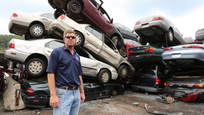 Ed Malone, vice president of Brookfield Resource Management in Elmsford, stands with junked cars that will be crushed and recycled.