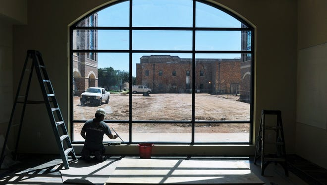 Jaimie Ochoa of SilvaFox cleans windows in a lounge area of the new Legacy Hall dormitory at Midwestern State University in August.